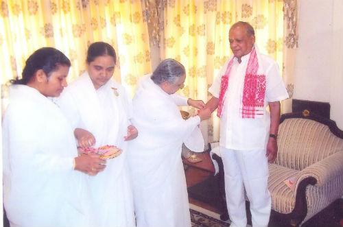 Tying Rakhi to Assam's Governor J. B. Patnaik