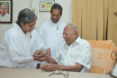B. K. Radha tying Rakhi to Justice V.R Krishna Iyer  in Kochi (Kerala)